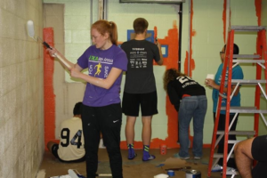 Impact Foundation volunteers paint the new impact closet at the middle school.